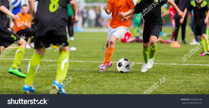 Stock-photo-young-boys-children-in-uniforms-playing-youth-soccer-football-game-tournament-horizontal-sport-394428136
