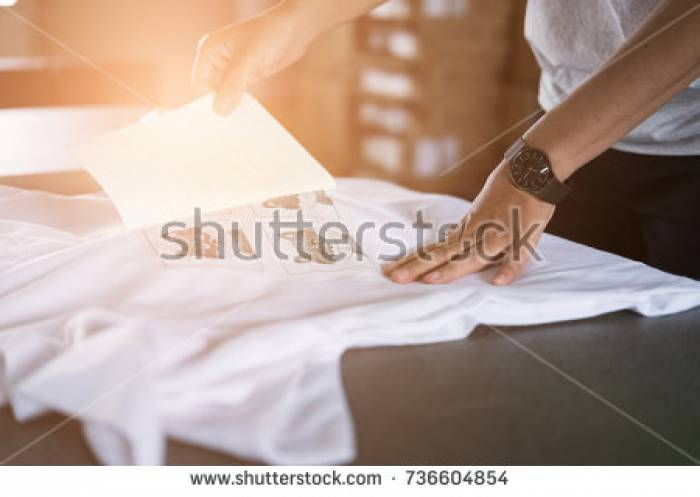 Stock-photo-young-woman-pull-out-paper-from-waterproof-film-on-fabric-worker-working-on-manual-screen-printing-736604854